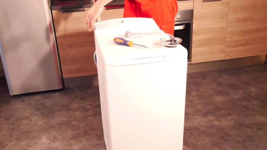 Déboîter le bandeau en haut de la machine à laver
