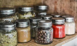 plusieurs pots d'herbes aromatiques posés dans une étagère en bois