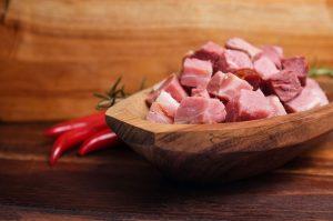 coupelle rempli de lardons avec du piment posé sur une table en bois