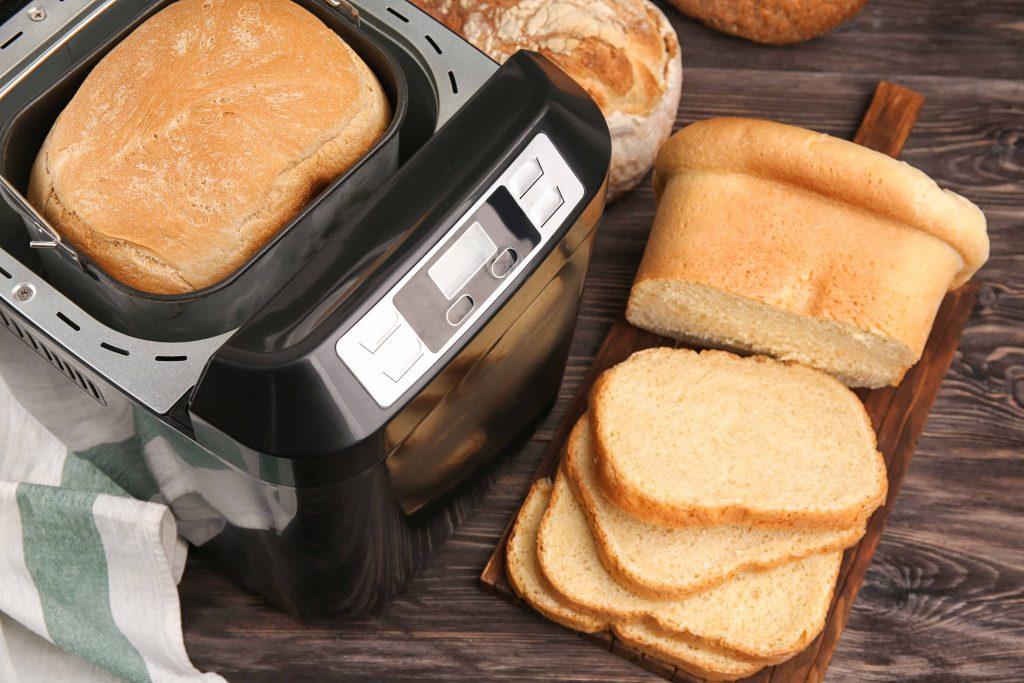machine à pain sur une table avec sur une planche du pain frais découpé