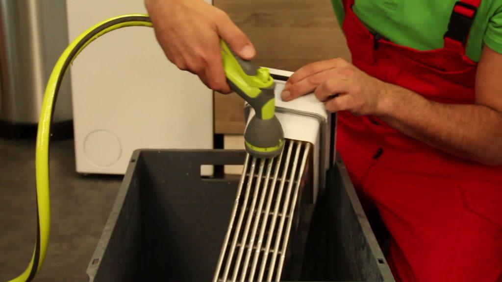 Nettoyage à la douchette du condenseur de sèche-linge