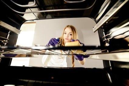 femme nettoie l'intérieur de son four avec une éponge