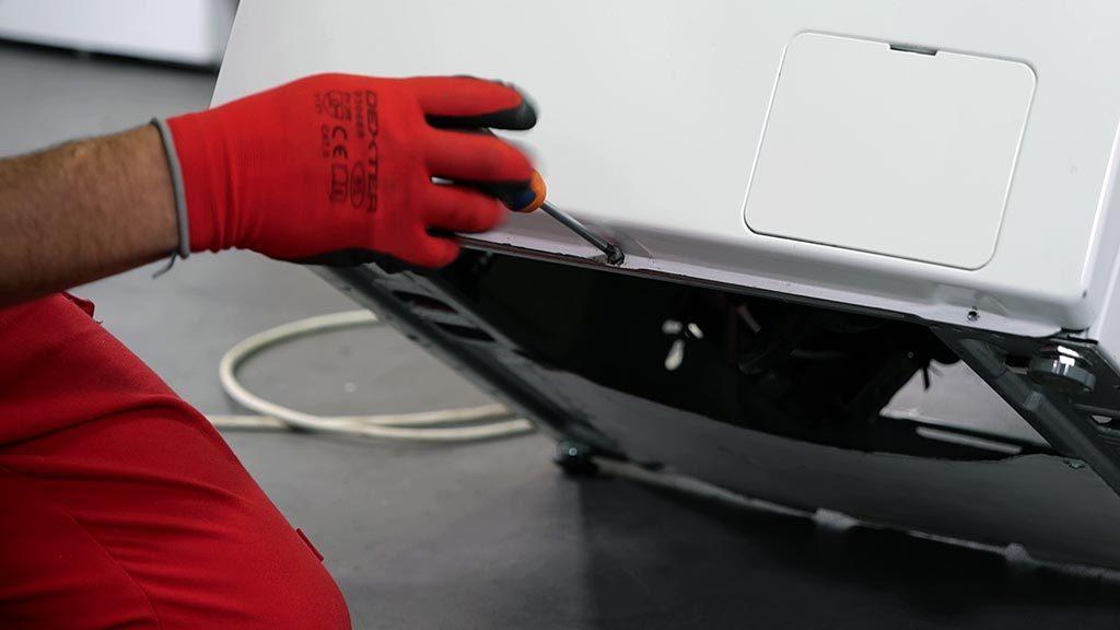 Retirer les vis situées sous le panneau avant du lave-linge