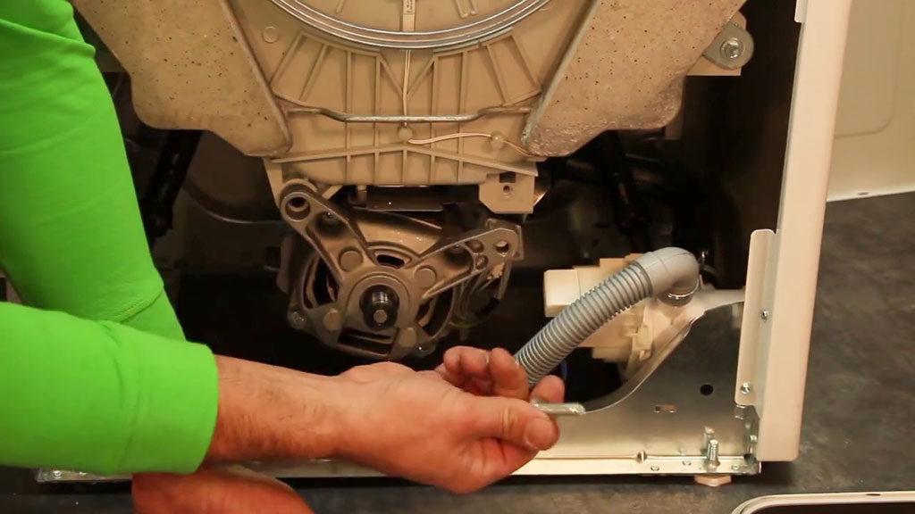 Retirer le ou les boutons maintenant le moteur dans le lave-linge top