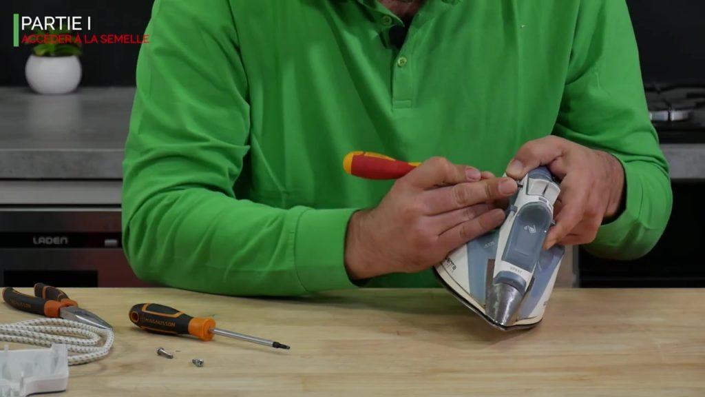 Déclipser la partie de controle du fer vapeur à l'aide d'un tournevis plat et faire levier