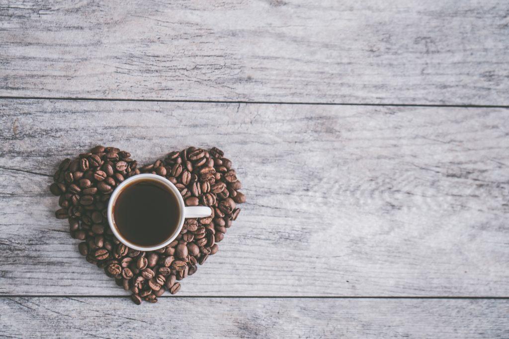 Tasse de café noir et grains de café en forme de coeur